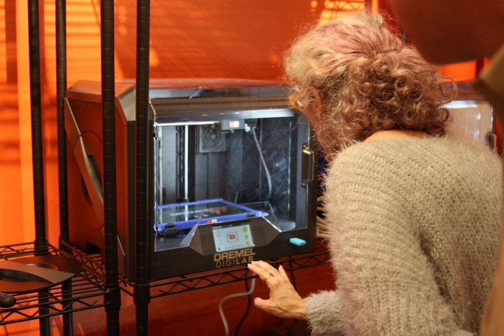 Woman watching a 3D printer print her project.